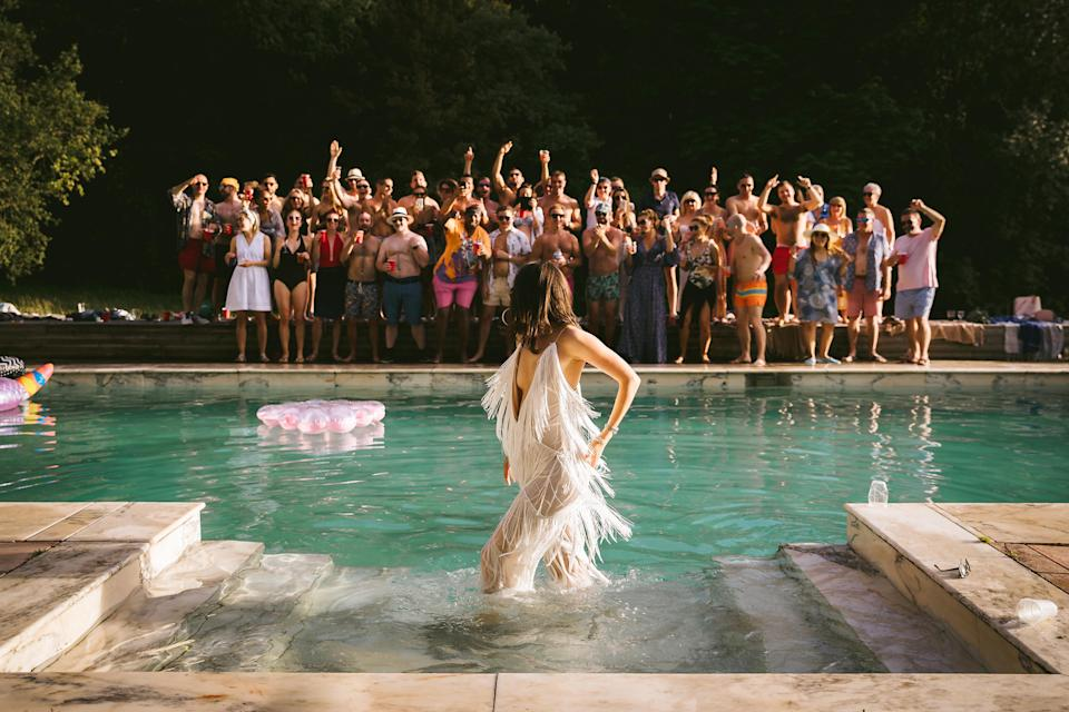 <p>A bride turns to face her wedding guests while standing in a swimming pool. <em>[Photo: <span>NIGEL JOHN / JUNEBUG WEDDINGS / CATERS]</span></em> </p>