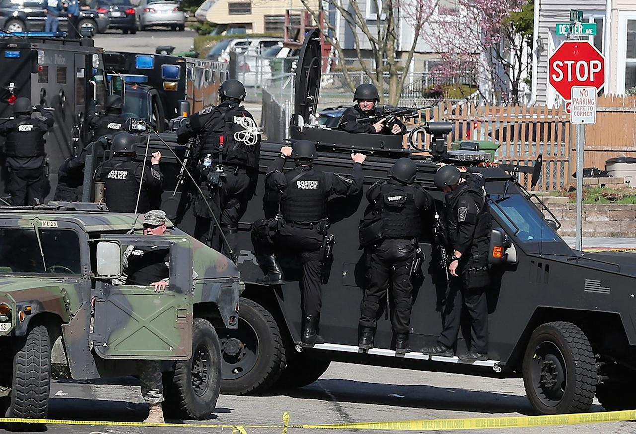WATERTOWN, MA - APRIL 19:  Members of a SWAT team search for 19-year-old bombing suspect Dzhokhar A. Tsarnaev on April 19, 2013 in Watertown, Massachusetts. After a car chase and shoot out with police, one suspect in the Boston Marathon bombing, Tamerlan Tsarnaev, 26, was shot and killed by police early morning April 19, and a manhunt is underway for his brother and second suspect, 19-year-old suspect Dzhokhar A. Tsarnaev. The two men, reportedly Chechen of origin, are suspects in the bombings at the Boston Marathon on April 15, that killed three people and wounded at least 170. (Photo by Mario Tama/Getty Images)