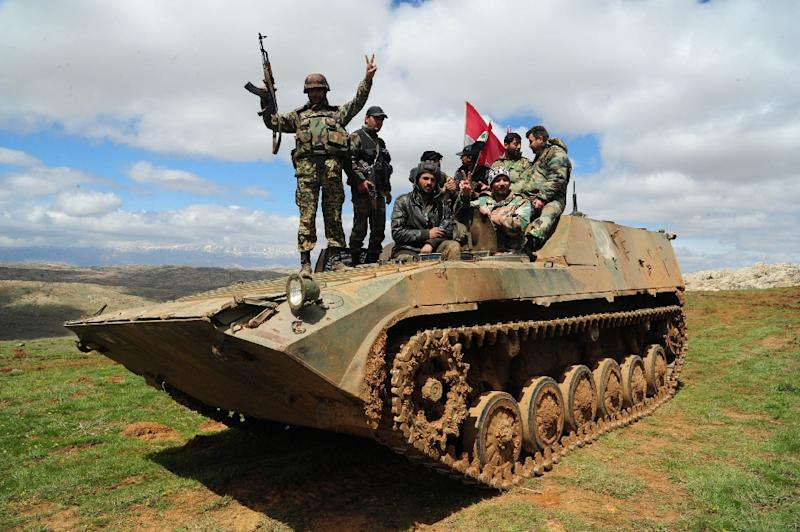 A picture released by the Syrian Arab News Agency on March 31, 2015, shows Syrian pro-government fighters sitting on an armoured vehicle in the mountains surrounding the city of Zabadani