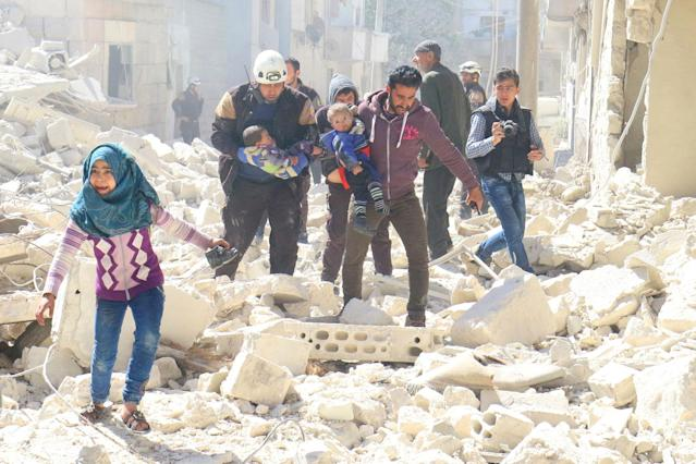 <p>MAR. 19, 2017 – People and a civil defence personnel carry children at a damaged site after an air strike on rebel-held Idlib city, Syria. Photo: Ammar Abdullah/Reuters) </p>