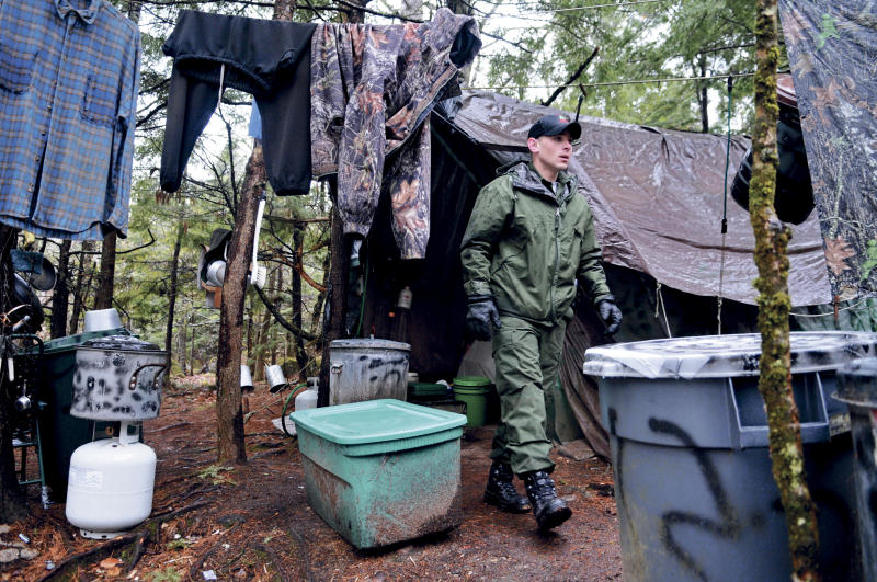 ROME, ME - APRIL 9: District Game Warden Aaron Cross exits Christopher Knight's camp Tuesday April 9, 2013 in a remote, wooded section of Rome after police inspected the site where Knight is believed to have lived since the 1990s. Police believe Knight, who went into the woods near Belgrade in 1986, was a hermit who committed hundreds of burglaries to sustain himself. (Photo by Andy Molloy via Getty Images)