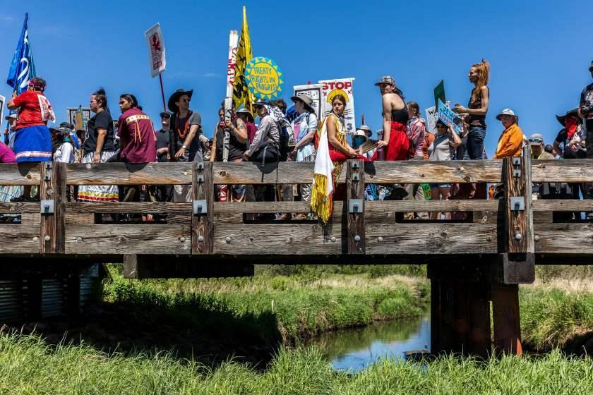TOPSHOT - Climate activist and Indigenous community members gather on top of the bridge after taking part in a traditional water ceremony during a rally and march to protest the construction of Enbridge Line 3 pipeline in Solvay, Minnesota on June 7, 2021. - Line 3 is an oil sands pipeline which runs from Hardisty, Alberta, Canada to Superior, Wisconsin in the United States. In 2014, a new route for the Line 3 pipeline was proposed to allow an increased volume of oil to be transported daily. While that project has been approved in Canada, Wisconsin, and North Dakota, it has sparked continued resistance from climate justice groups and Native American communities in Minnesota. While many people are concerned about potential oil spills along Line 3, some Native American communities in Minnesota have opposed the project on the basis of treaty rights and calling President Biden to revoke the permits and halt construction. (Photo by Kerem Yucel / AFP) (Photo by KEREM YUCEL/AFP via Getty Images)