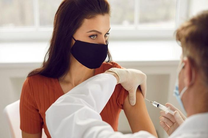 Woman in medical protective mask getting injection in arm vaccination.