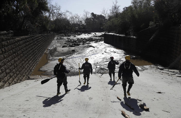<p>Members of the Los Angeles County Fire Department Search and Rescue crew walk toward flooded waters in Montecito, Calif., Wednesday, Jan. 10, 2018. (Photo: Marcio Jose Sanchez/AP) </p>