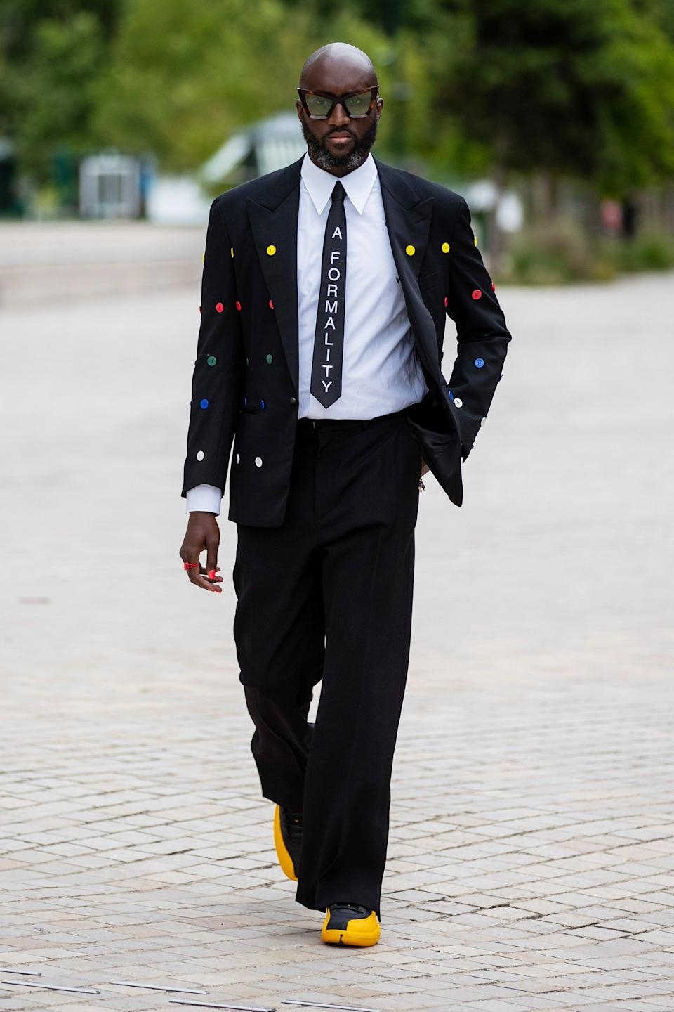 """Off-White designer Virgil Abloh made a black suit look summer-appropriate with a rainbow-hued polka dot print, a tie with """"A Formality"""" emblazoned on it, and colorful shoes. <span class=""""copyright"""">Photo: Christian Vierig/Getty Images.</span>"""