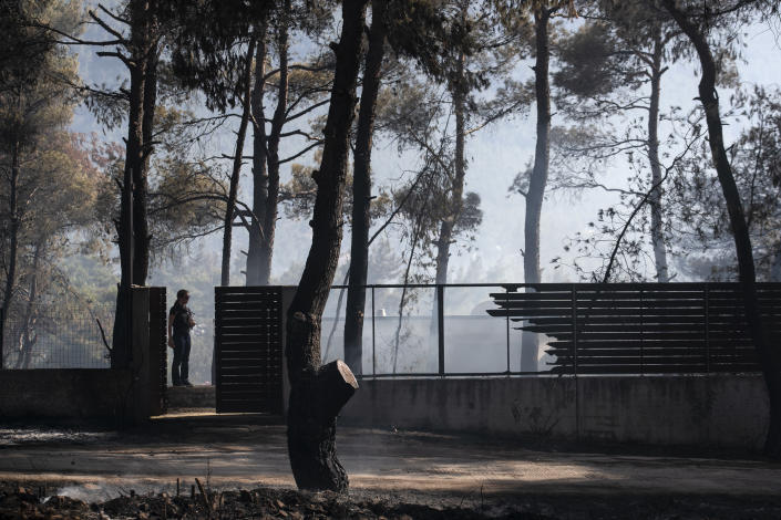 A resident stands at the entrance of a damaged house at Dionysos northern suburb of Athens, on Tuesday, July 27, 2021. Greek authorities have evacuated several areas north of Athens as a wildfire swept through a hillside forest and threatened homes despite a large operation mounted by firefighters. (AP Photo/Yorgos Karahalis)