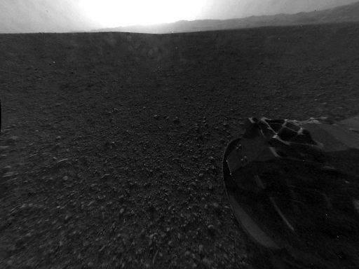 Image provided by NASA on August 7 shows one of the first images of Mars taken by a rear Hazard-Avoidance camera on the Curiosity rover. On Wednesday, NASA plans to lift the rover's remote sensing mast for the first time. More images, including color high-resolution shots, are expected to arrive in the coming days