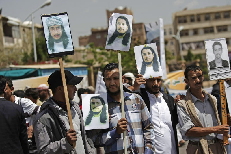 Yemeni protestors hold photos of their relatives detained in Guantanamo Bay prison during a demonstration in front of the U.S. embassy demanding their release, in Sanaa, Yemen, Monday, April 1, 2013. (AP Photo/Hani Mohammed)