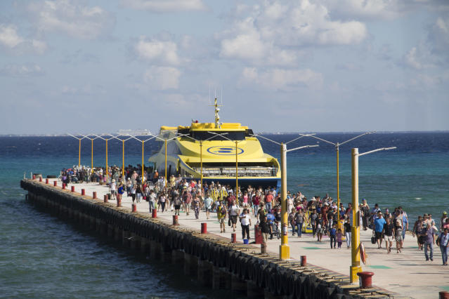 """In this Friday, March 2, 2018 photo, tourists and passengers disembark from a ferry on to the wharf on Playa del Carmen, Mexico. In a notice posted Friday, March 9, on its website, the U.S. Embassy in Mexico has narrowed its travel warning for the Caribbean resort city of Playa del Carmen amid what it calls an unspecified """"ongoing security threat"""" just as the spring holiday season is kicking into high gear. (AP Photo/Gabriel Alcocer)"""