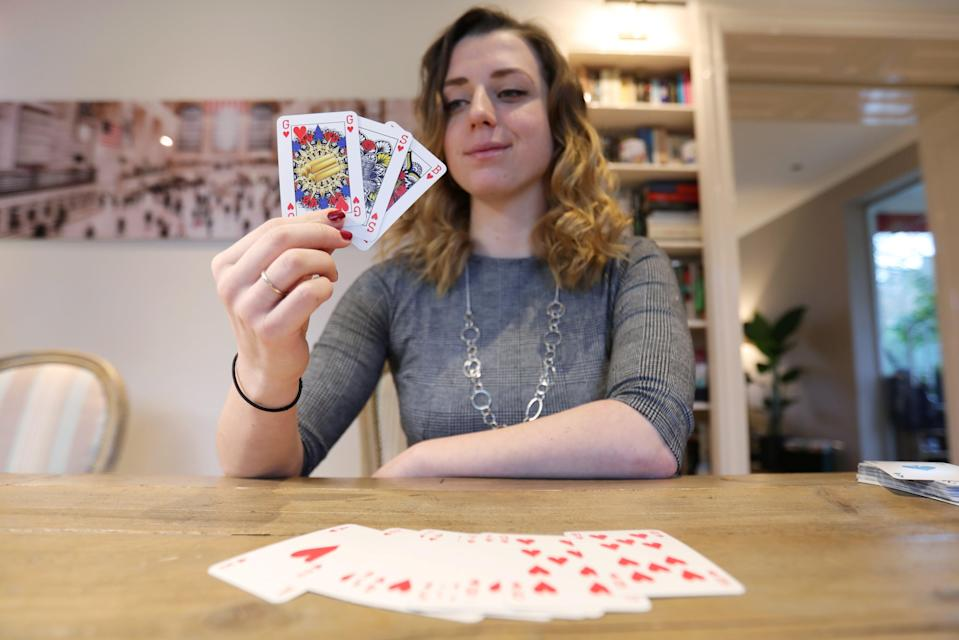 <p>Indy Mellink, 23, shows off the genderless playing cards that she designed </p> (REUTERS)