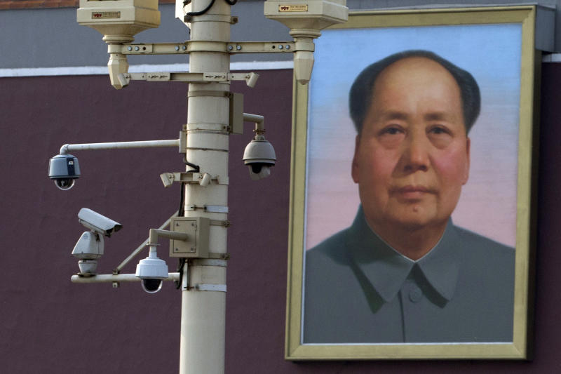 A portrait of late Chinese leader Mao Zedong is displayed near security cameras on the eve of the 24th anniversary of the bloody military crackdown on protesters near Tiananmen Gate in Beijing Monday, June 3, 2013. Activists in China are taking to social media to urge the public to wear black on the 24th anniversary of the bloody military crackdown on protesters who had camped out for weeks on Tiananmen Square. (AP Photo/Ng Han Guan)