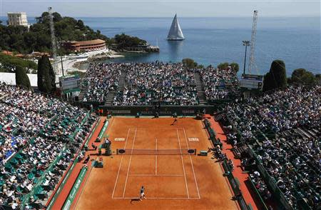 A sail boat passes by the central court as Roger Federer of Switzerland (bottom) prepares to serve against Lukas Rosol of the Czech Republic during the Monte Carlo Masters in Monaco April 17, 2014. REUTERS/Eric Gaillard