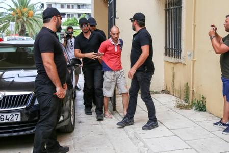 Plain-clothes police officers escort the suspect for the murder of American biologist Suzanne Eaton to the prosecutor in Chania, on the island of Crete