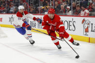 Detroit Red Wings center Dylan Larkin (71) protects the puck from Montreal Canadiens defenseman Xavier Ouellet (61) during the second period of an NHL hockey game Tuesday, Feb. 18, 2020, in Detroit. (AP Photo/Paul Sancya)