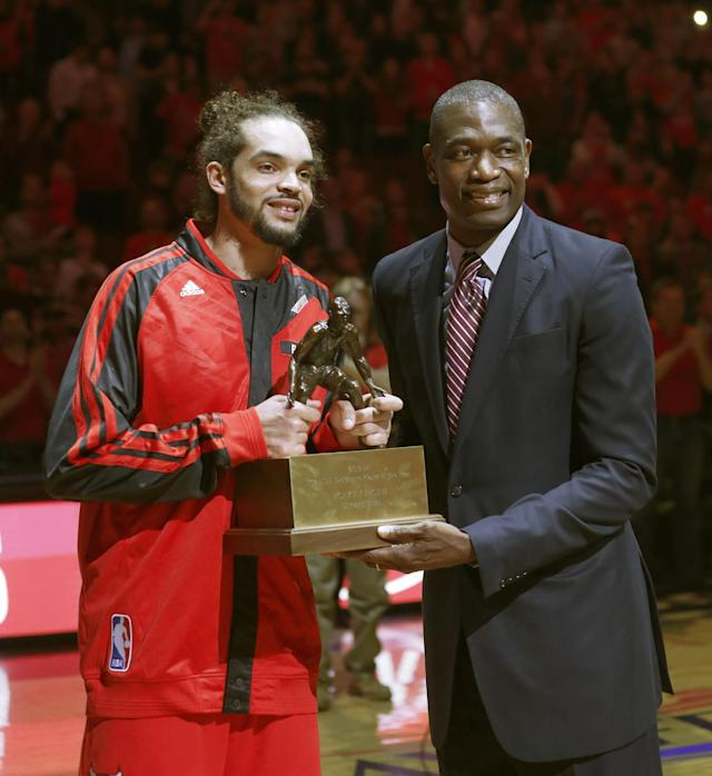 Chicago Bulls center Joakim Noah, left, accepts the 2014 Defensive Player Of The Year Award from Dikembe Mutombo before Game 2 in an opening-round NBA basketball playoff series game against the Washington Wizards Tuesday, April 22, 2014, in Chicago. (AP Photo/Charles Rex Arbogast)