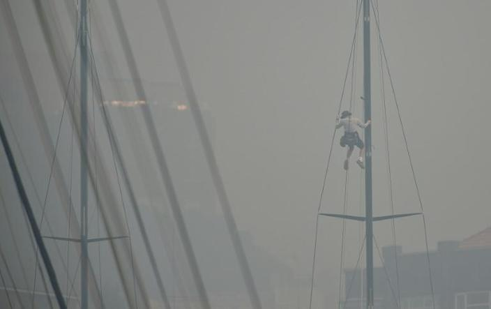 A sailor climbs the mast of a yacht enveloped in haze caused by nearby bushfires at the Cruising Yacht Club of Australia in Sydney on December 10, 2019 (AFP Photo/PETER PARKS)