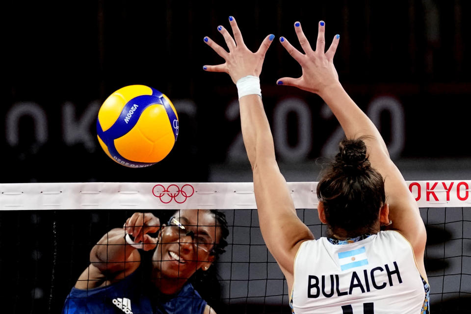 United States' Foluke Akinradewo, left, hits the ball past Argentina's Daniela Bulaich Simian during the women's volleyball preliminary round pool B match between United States and Argentina at the 2020 Summer Olympics, Sunday, July 25, 2021, in Tokyo, Japan. (AP Photo/Frank Augstein)