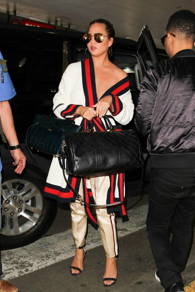 """<p>Leave it to Chrissy Teigen to make loungewear look ultra luxe. On Thursday, the model sashayed through LAX in a fresh-off-the runway Gucci look. She combined a $6,000 striped """"Blind For Love"""" cardigan with a pair of $1,100 silk pants from the brand's most-recent collection. A pair of killer heels, a Celine bag and gold Linda Farrow aviators completed the look. </p>"""
