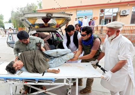 Men carry an injured person to a hospital after a bomb blast at a mosque, in Jalalabad, Afghanistan
