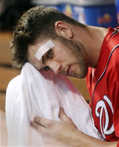 Washington Nationals' Bryce Harper wipes his face in the dugout during the fourth inning of a baseball game against the Cincinnati Reds, Saturday, May 12, 2012, in Cincinnati. Harper cut his forehead Friday night breaking a bat off the field. (AP Photo/Al Behrman)