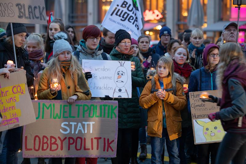 """20 December 2019, Thuringia, Erfurt: Participants of a Fridays for Future """"light demo"""" under the motto """"A light in the darkness - climate justice now!"""" walk through the city centre with candles and posters. With this campaign, the students and participants are also looking back on a year of Fridays for Future Erfurt. Photo: Michael Reichel/dpa-Zentralbild/dpa (Photo by Michael Reichel/picture alliance via Getty Images)"""