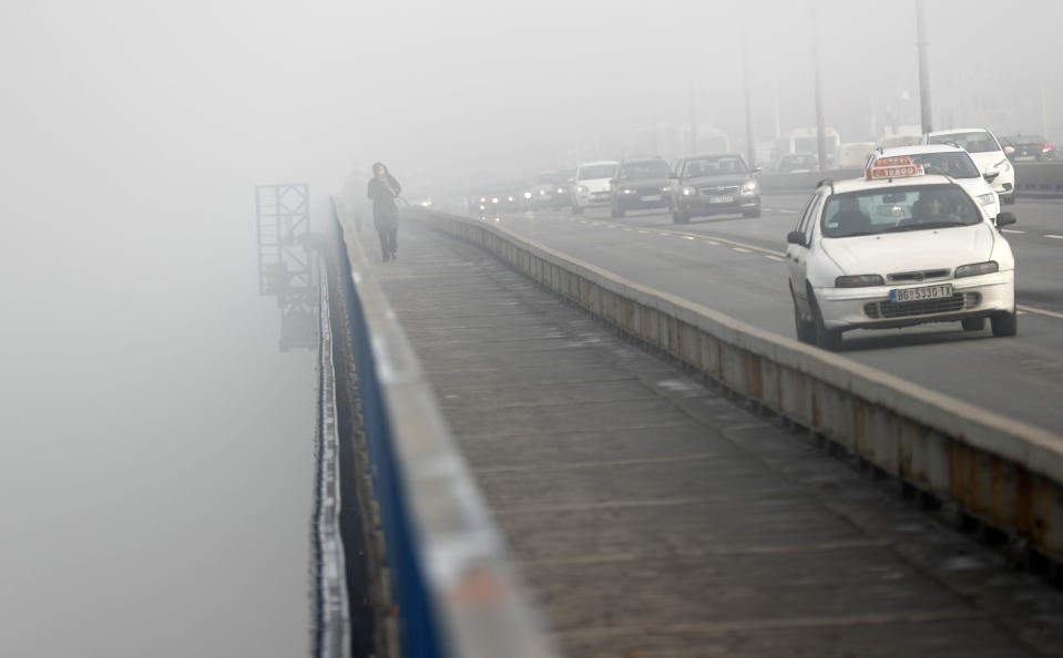 A girl walks across a bridge in Belgrade, Serbia, Wednesday, Jan. 15, 2020. Serbia's government on Wednesday called an emergency meeting, as many cities throughout the Balkans have been hit by dangerous levels of air pollution in recent days, prompting residents' anger and government warnings to stay indoors and avoid physical activity. (AP Photo/Darko Vojinovic)