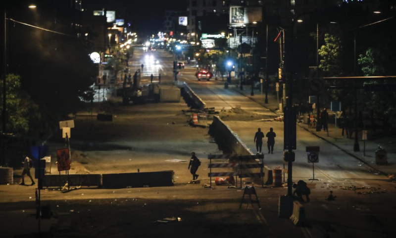 Pictured is a street in Minneapolis with debris strewn across it at night.