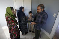 Abdul, right, who worked as a mechanic before he left Kabul, Afghanistan with his family about a month ago, shows his family a donated tea kettle as they stand in the kitchen of a rental house, Thursday, Sept. 16, 2021, that has been provided as a place for them to stay in Seattle. The home is owned by Thuy Do, who was nine years old when her family arrived in the United States from Vietnam in the 1980s. Now Do and her husband have offered their vacant rental home to refugee resettlement groups to house newly arriving Afghans in need of a place to stay. (AP Photo/Ted S. Warren)