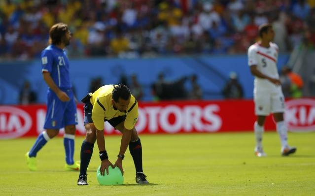 Referee Enrique Osses of Chile picks up a balloon which landed on the pitch during the 2014 World Cup Group D soccer match between Italy and Costa Rica at the Pernambuco arena in Recife June 20, 2014. REUTERS/Brian Snyder (BRAZIL - Tags: SOCCER SPORT WORLD CUP)