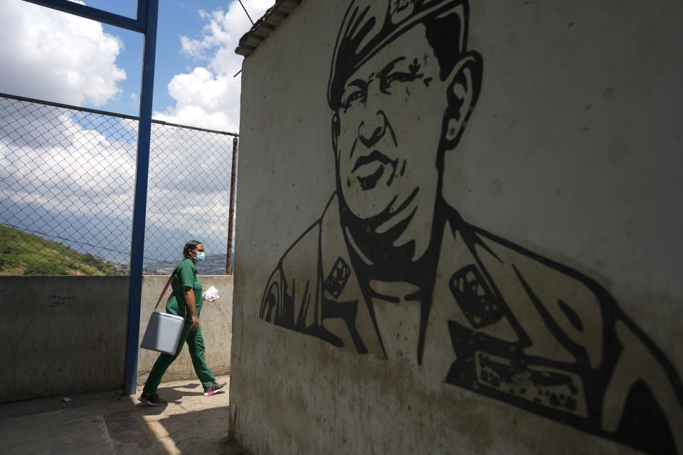 Nurse Genny Zorrilla walks with a cooler containing Sinopharm COVID-19 vaccines past a mural of late president Hugo Chavez, during house to house vaccinations in the popular neighborhood of El Valle in Caracas, Venezuela, Monday, Sept. 27, 2021. According to the Pan American Health Organization Venezuela one of the least vaccinated countries in the continent, is seeing a growing uptick in caseloads, unlike other countries in the region where cases are dropping. (AP Photo/Ariana Cubillos)