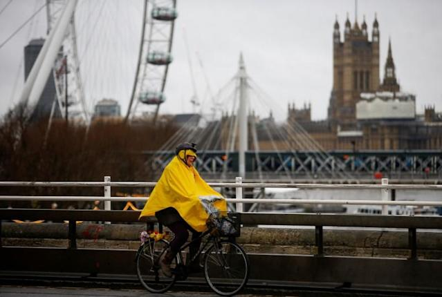 FILE PHOTO: Woman cycles across Waterloo Bridge during wet and windy weather in London