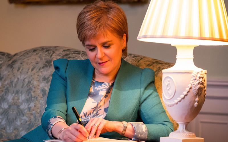 First Minister Nicola Sturgeon in the Drawing Room in Bute House, Edinburgh, working on the final draft of her Section 30 letter to the Prime Minister Theresa May formally requesting a second Scottish independence referendum - Credit: PA