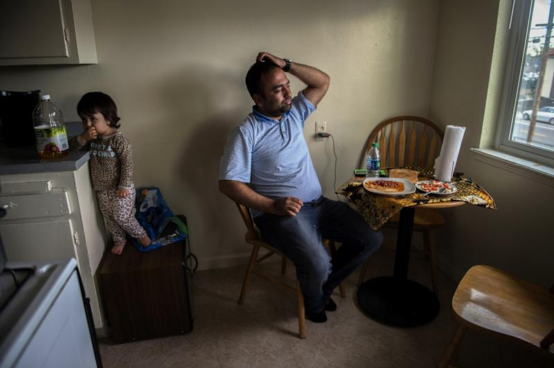 "Faisal Razmal eats a meager meal of canned beans and ponders his future with his daughter, Bib Maryam, nearby on Tues., Mar., 1, 2016 in Sacramento, Calif. He lost his security job and was searching for another job. He had tried dish washing, car washing and was getting a little money from a friend who he walked security with at night. The other jobs were temporary and he says he paid more money in gas to get to them than what he made. He said he owes $650 on his credit card, and more than $4,000 to Afghan friends who have loaned him money to pay their rent. ""I've gotten three eviction notices with three days notice,"" he said. ""I have no food, no money, no nothing. I applied for disability nine months ago and haven't received one penny."" He says he needs a job."