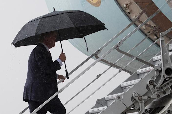 US President Donald Trump boards Air Force One under heavy rain at Andrews Air Force Base, Maryland, April 6, 2017 to head to Florida to meet with Chinese President Xi Jinping (AFP Photo/JIM WATSON)