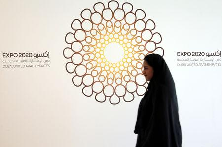 FILE PHOTO: A woman walks past the logo of Expo 2020 in Dubai