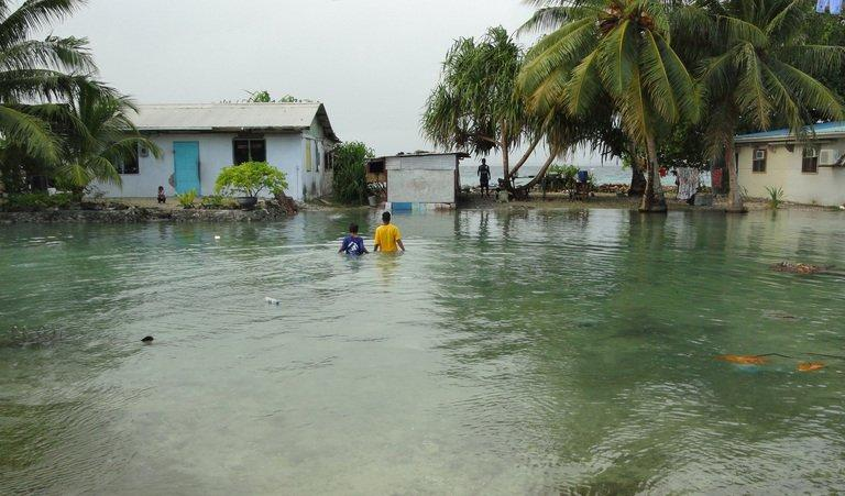 Residents wade through flooding caused by high ocean tides on Majuro Atoll, the capital of the Marshall Islands, in 2011