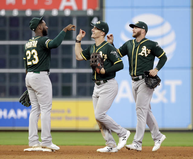 Oakland Athletics' Jurickson Profar (23), Mark Canha, center, and Robbie Grossman celebrate after a baseball game against the Houston Astros Tuesday, Sept. 10, 2019, in Houston. The Athletics won 21-7. (AP Photo/David J. Phillip)