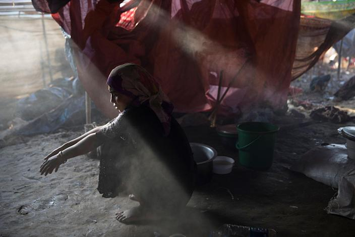 <p>Sajida Begum, 18, sits in her makeshift tent washing rice for dinner as smoke catches the late afternoon light on September 25, in Thainkhali camp, Cox's Bazar, Bangladesh. (Photograph by Paula Bronstein/Getty Images) </p>