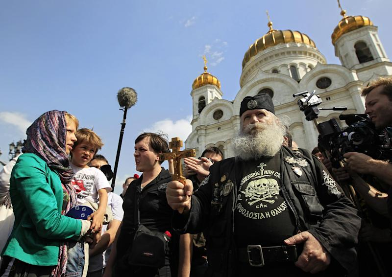 """An opposition activist with her child stands in front of Orthodox militant group members standing in line in front of the Moscow's Christ the Savior Cathedral to prevent access of opposition to the Cathedral in Moscow, Sunday, April 29, 2012. Opposition activists planned to pray to Holy Mother to deliver Russia from Vladimir Putin. They planned to repeat the """"punk prayer"""" by five members of the feminist band Pussy Riot briefly who seized the pulpit of Moscow's Christ the Savior Cathedral in February and chanted """"Mother Mary, drive Putin away."""" Three band members have been arrested and now face up to seven years in jail on charges of hooliganism. (AP Photo/Sergey Ponomarev)"""