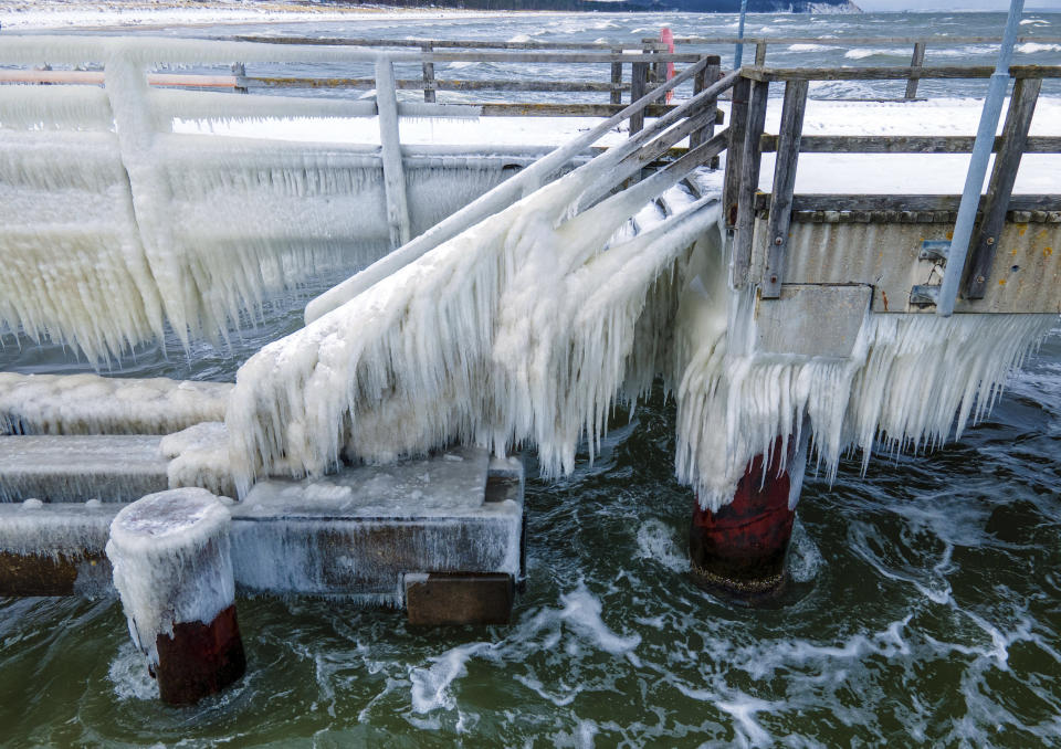 A thick layer of ice has formed at temperatures of minus five degrees on the pier on the island of Ruegen, Germany, Thursday, Feb.11, 2021. The bridge is closed to pedestrians because of the icing. (Jens Buettner/dpa via AP)
