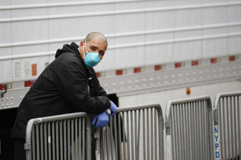 A medical worker wearing personal protective equipment due to COVID-19 concerns rests beside a refrigerated container truck functioning as a makeshift morgue, Tuesday, March 31, 2020, at Brooklyn Hospital Center in the Brooklyn borough of New York. The new coronavirus causes mild or moderate symptoms for most people, but for some, especially older adults and people with existing health problems, it can cause more severe illness or death. (AP Photo/John Minchillo)