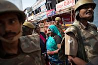 Hindu devotees walk past security personnel standing guard in a street after Supreme Court's verdict on a disputed religious site in Ayodhya, India, November 9, 2019. REUTERS/Danish Siddiqui