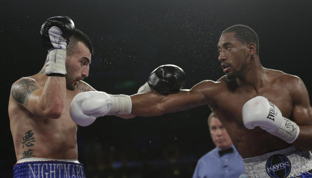 Demetrius Andrade, right, hits Vanes Martirosyan, left, during round 7 of a WBO junior middleweight title bout, Saturday, Nov. 9, 2013, in Corpus Christi, Texas. (AP Photo/Eric Gay)