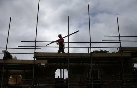 FILE PHOTO: A builder assembles scaffolding as he works on new homes, in south London June 3, 2014. REUTERS/Andrew Winning/File Photo