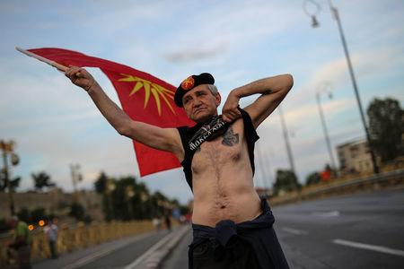 A supporter of opposition party VMRO-DPMNE waves a flag and shows his tattoo as he takes part in a protest over compromise solution in Macedonia's dispute with Greece over the country's name, in Skopje, Macedonia, June 2, 2018. REUTERS/Marko Djurica