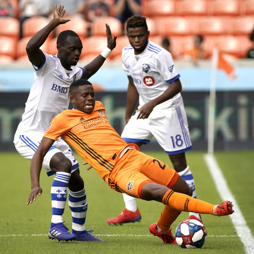 Houston Dynamo's Oscar Garcia, center, tries to keep the ball from Montreal Impact's Michael Azira, left, during the first half of an MLS soccer match Saturday, March 9, 2019, in Houston. (AP Photo/David J. Phillip)