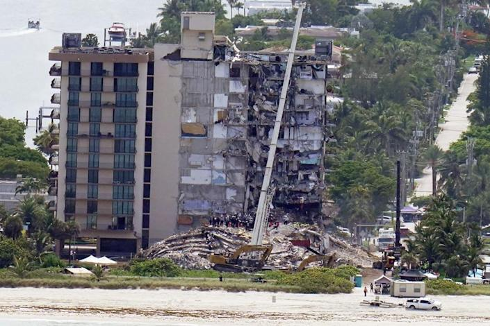 Workers search in the rubble at the Champlain Towers South Condo, Saturday, June 26, 2021, in Surfside, Fla. (AP Photo/Gerald Herbert)