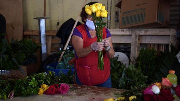 PHOTO: A woman prepares a flower bouquetat a shop in the Los Angeles Flower District, May 8, 2020, after the county allowed retail establishments to open ahead of Mother's Day. (Agustin Paullier/AFP via Getty Images, FILE)
