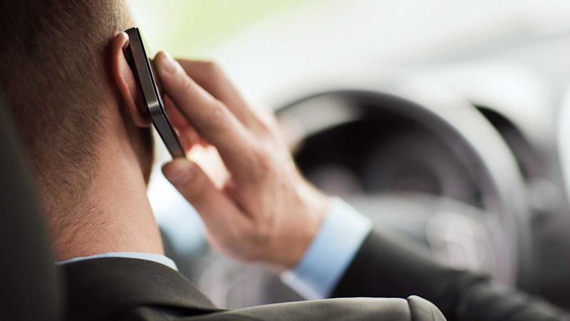 Man using phone while driving car