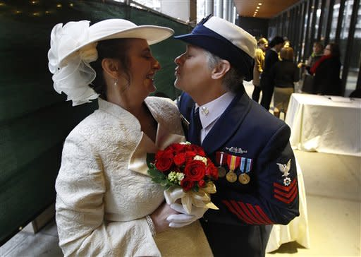 Retired U.S. Coast Guard Petty Officer 1st Class Nancy Monahan, right, wears her dress uniform as she leans to kiss her soon-to-be bride Deb Needham while they wait at Seattle City Hall to become among the first gay couples to legally wed in Washington state, Sunday, Dec. 9, 2012, in Seattle. The couple is from Renton, Wash. Gov. Chris Gregoire signed a voter-approved law legalizing gay marriage Dec. 5 and weddings for gay and lesbian couples began in Washington on Sunday, following the three-day waiting period after marriage licenses were issued earlier in the week. (AP Photo/Elaine Thompson)